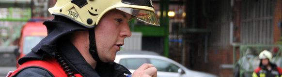 Der Gruppenführer des Löschfahrzeugs gibt über Funk Befehle an seine Mannschaft.